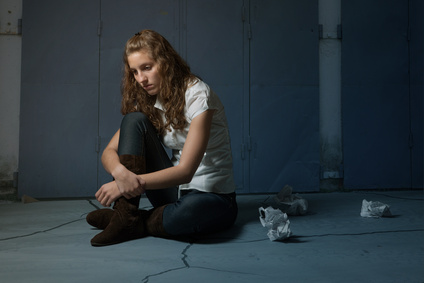 Girl sad sitting on floor due to abandonment divorce in New York