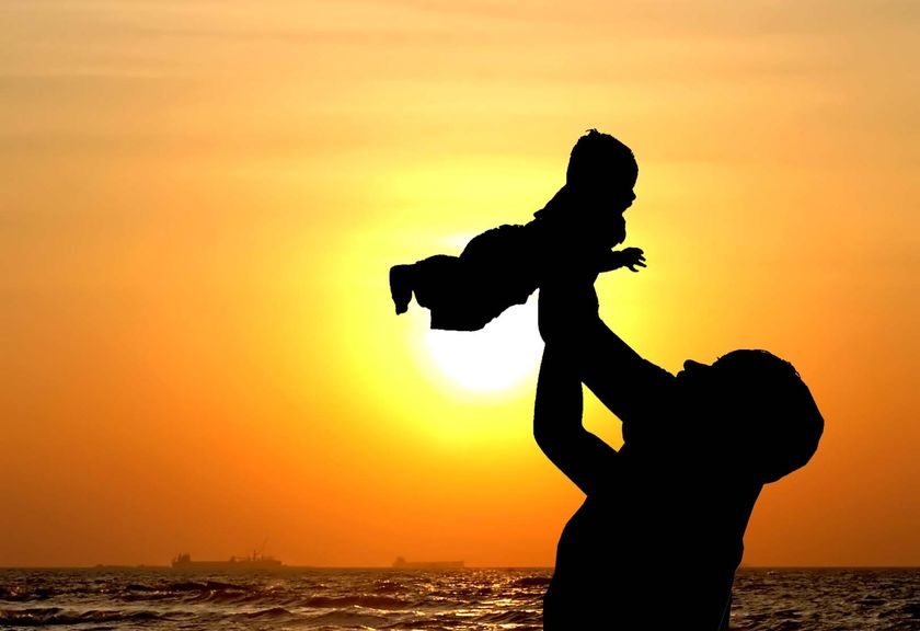 parent holding child in sunset as example of adoption guardianship