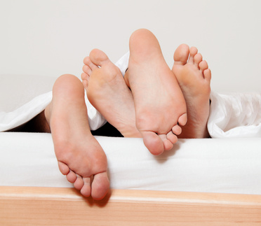 Divorce through adultery shown by pairs of feet at the end of a bed